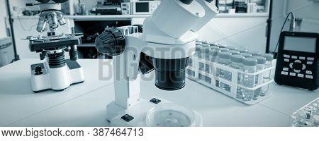 Science microscope on lab bench. Microbiology laboratory. Blue toned image of binocular microscope