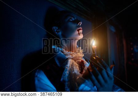 A bloodthirsty vampire aristocrat standing in the castle with a candle in his hands. 19th century style. Halloween.