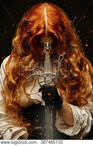 A redhead woman with a war sword (rapier) prays while holding a sword . The heroine of a historical adventure novel.