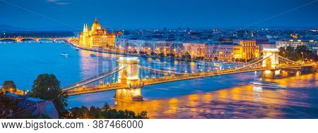 Scenic top view of the Hungarian Parliament and Chain Bridge on the Danube river at night. Location place Budapest, Hungary, Europe. Photo of popular tourist attraction of the world. Beauty of earth.