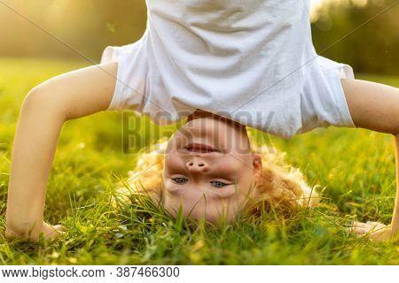 Little boy standing upside down in park