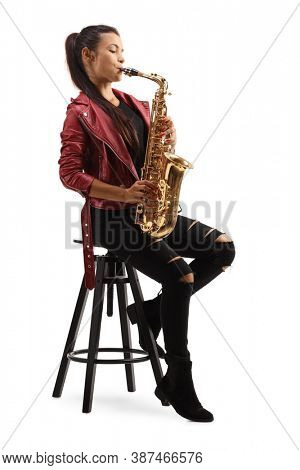 Full length portrait of a young female in a red leather jacket playing saxophone and sitting on a chair isolated on white background