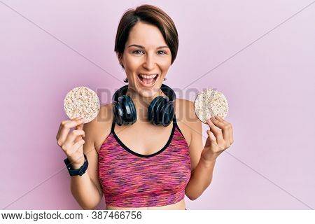 Young brunette woman with short hair wearing sportswear holding rice cakes smiling and laughing hard out loud because funny crazy joke.