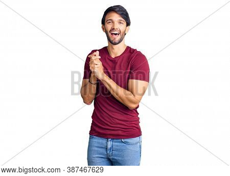 Handsome hispanic man wearing casual clothes clapping and applauding happy and joyful, smiling proud hands together