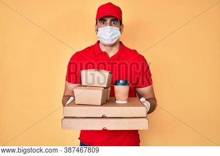 Handsome hispanic man with beard holding delivery food wearing medical mask puffing cheeks with funny face. mouth inflated with air, catching air.