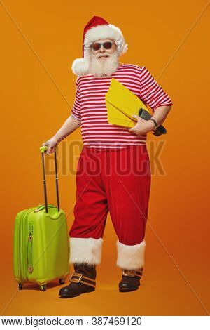 Jolly funny Santa Claus goes on vacation. Christmas Holidays, tourist trips to hot tropical countries. Bright yellow background. Copy space.