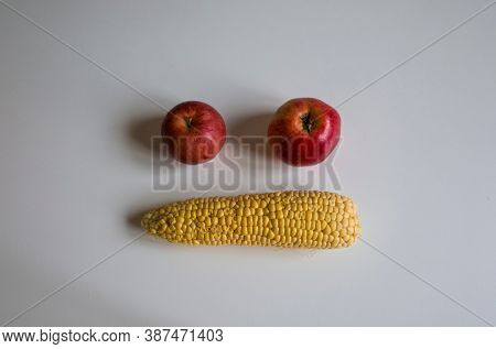Yellow peeled cob of sweet corn and two red apples formed face emoji two eyes and mouth on white table. Homegrown real organic vegetables not perfect look. Selective short focus, Natural light