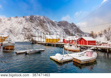 Traditional red and yellow wooden houses, rorbuer in the small fishing village of Nusfjord, Lofoten islands, Norway, Europe. Noewegian fjord with fish boats