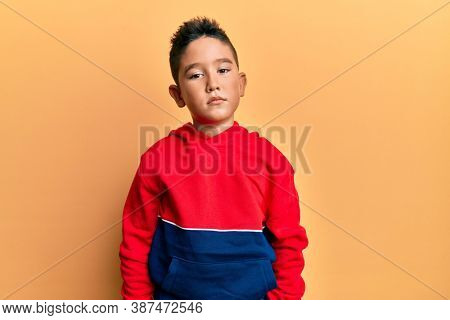 Little boy hispanic kid wearing casual sweatshirt with serious expression on face. simple and natural looking at the camera.