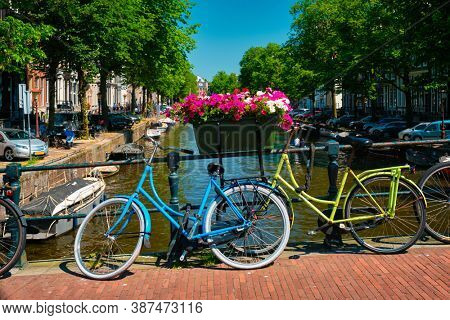 Typical Amsterdam view - Amsterdam canal with boats and parked bicycles on a bridge with flowers. Amsterdam, Netherlands