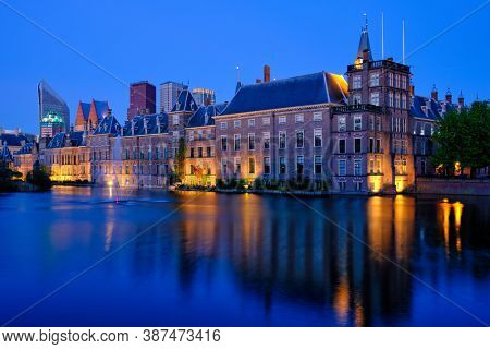 View of the Binnenhof House of Parliament and the Hofvijver lake with downtown skyscrapers in background illuminated in the evening. The Hague, Netherlands