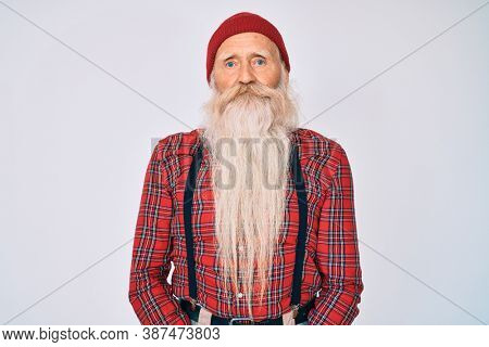 Old senior man with grey hair and long beard wearing hipster look with wool cap relaxed with serious expression on face. simple and natural looking at the camera.