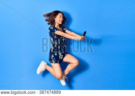 Young beautiful chinese woman jumping with smile on face. Make selfie by smartphone over isolated blue background