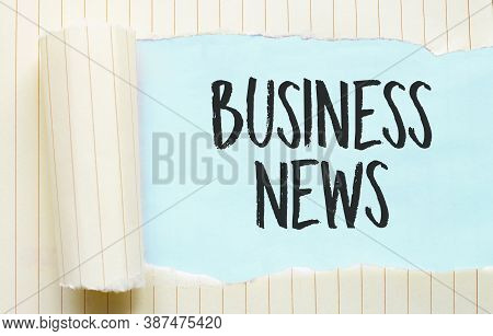 The Text Business News Appearing Behind Torn White Paper