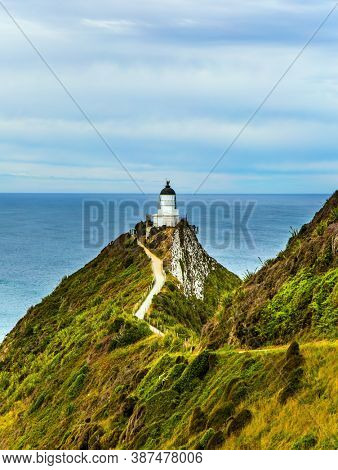 Nugget Point Lighthouse on the picturesque Cape Nugget. South Island, New Zealand. The picturesque coast of the Pacific Ocean. The concept of active, environmental and photo tourism