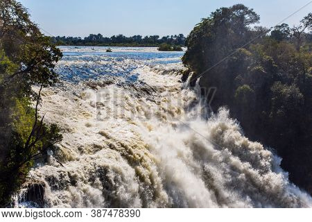 Journey after the wet season. Dizzy Victoria Falls. The waterfall is located on the Zambezi River, in Victoria National Park, on the border between Zambia and Zimbabwe.