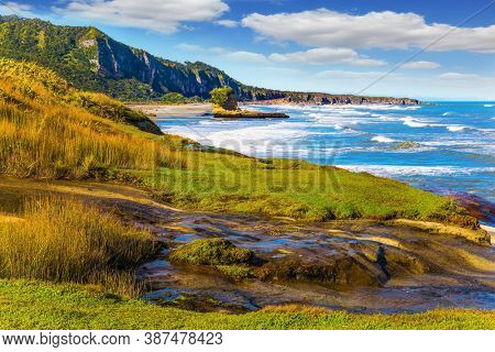Powerful ocean surf. Incredible journey to the ends of the world. New Zealand. The picturesque Pacific coast of the South Island. The concept of ecological, active and photo tourism