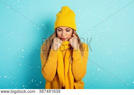 Woman Keeps Warm With Scarf And Hat In Winter. Cyan Background