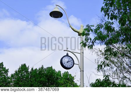 City Lamppost With A Modern Lamp And Round Street Clock Showing 02:05 P.m., Against Blue Sky Surroun