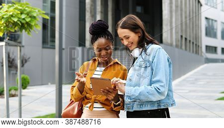 Mixed-races Females Talking And Watching Something On Tablet Device At Street In City. Beautiful Mul