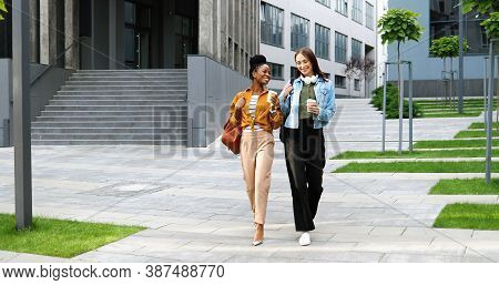 Mixed-races Young Pretty Females, Best Friends Talking Cheerfully And Walking With Cups Of Coffee To