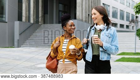 Mixed-races Young Pretty Females Best Friends Talking Cheerfully And Walking With Cups Of Coffee To-