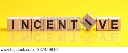 Word Incentive Is Made Of Wooden Building Blocks Lying On The Table And On A Light Yellow Background