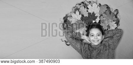 Im Hairdresser. Happy Girl With Colorful Leaves In Hair. Small Child In Autumn Mood On Brown Backgro