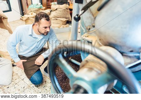 Man operating coffee roaster in his factory