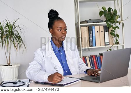 Serious African Female Doctor Watching Online Medical Webinar Seminar Training Elearning On Laptop M