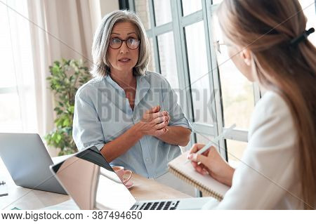 Mature Old Female Mentor Or Manager Training Young Intern Explaining Sharing Professional Skills In