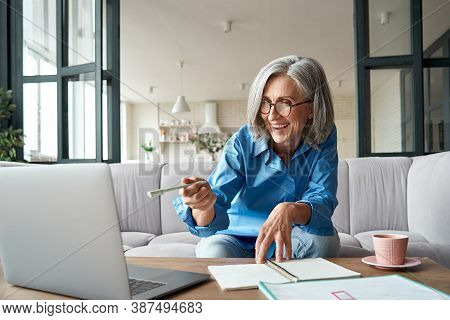 Happy Mature Older Woman Video Calling On Laptop Working From Home. Smiling 60s Middle Aged Business