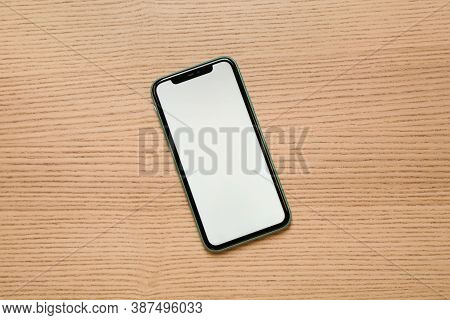 Mykolaiv, Ukraine - July 07, 2020: Iphone 11 On Wooden Background, Top View. Mockup For Design