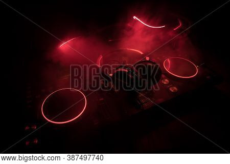 Dj Console Deejay-mixing Desk In Dark With Colorful Light. Mixer Equipment Entertainment Dj Station.