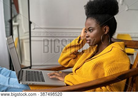 Thoughtful Serious Black Biracial Woman In Yellow Cardigan Remote Studying, Working Online On Laptop