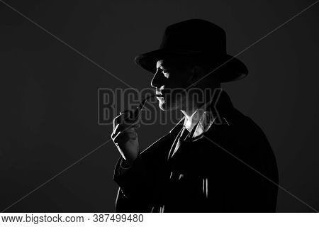 Old Fashioned Detective With Smoking Pipe On Dark Background, Black And White Effect