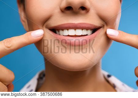 Young Woman With Beautiful Smile On Blue Background, Closeup. Cosmetic Dentistry