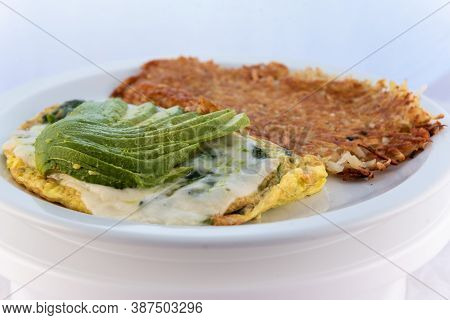 Generous Serving Meal Of A Hearty Avocado Omelette Covered With Gravy Combined With Hash Browns.