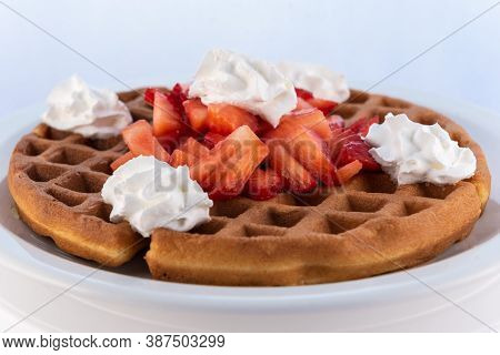 Generous Serving Meal Of A Hearty Strawberry Waffle Decorated With Whipped Cream On Round Plate.