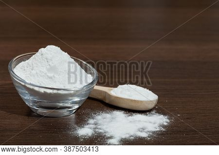Baking Soda - Glass Bowl And Wooden Spoon With Baking Soda; On Dark Wooden Background.