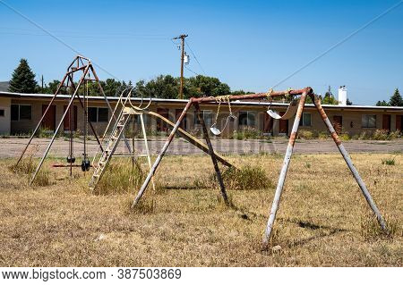 Rusty Playground Equipment With A Swingset Sits In A Courtyard Of An Abandoned Motel
