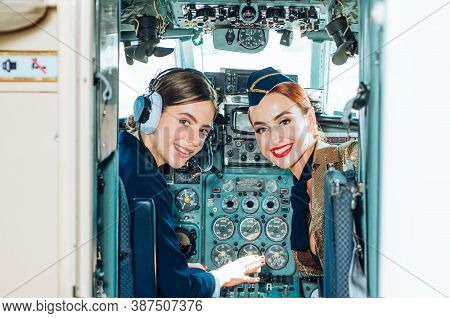 Back View From The Inside Of The Plane. Portrait Of Two Attractive Young Women Pilots With Headset P