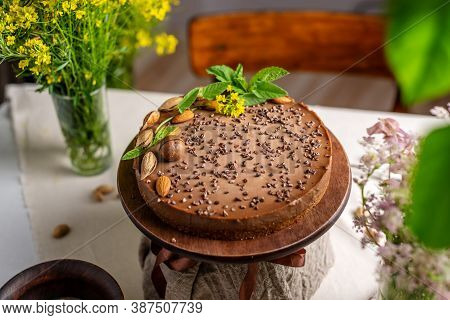Delicious Mousse Nut Cake Decorated With Nuts And Green Leaves. Concept Of Delicious And Healthy Des
