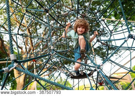 Insurance Kids. Happy Little Child Boy Sitting On The Web On Playground And Ready To Jump. Happy Kid