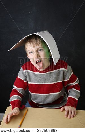Student acting up and misbehaving during learning time with his notebook on his head