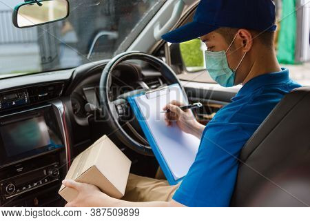 Asian Delivery Courier Young Man Driver Inside The Van Car With Parcel Post Boxes Checking Amount He