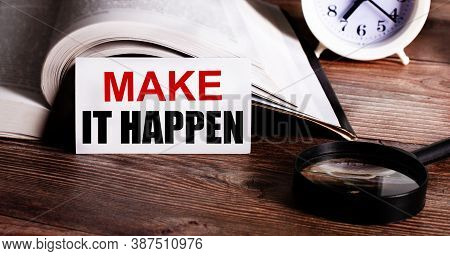 Make It Happen Written On A White Card Near An Open Book, An Alarm Clock And A Magnifying Glass On A