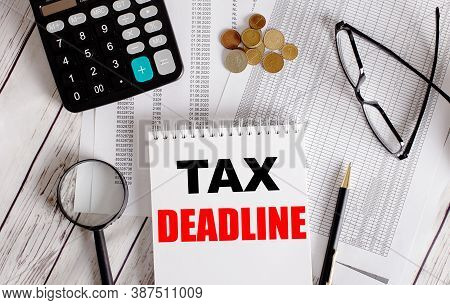 Tax Deadline Is Written In A Notebook Against The Background Of Reports Near Glasses, Calculator, Co