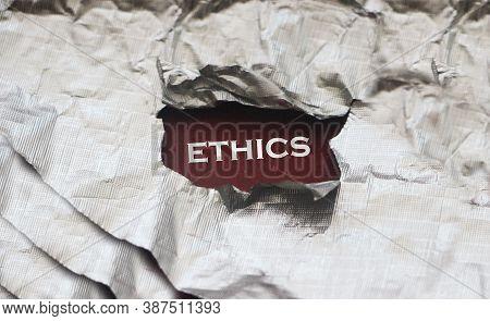 Ethics Word Written Under Torn Silver Foil Paper. Business Social Concept