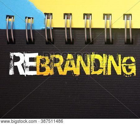 Rebranding Word On A Page Of Spiral Copybook White And Yellow On Black. Branding Marketing Business